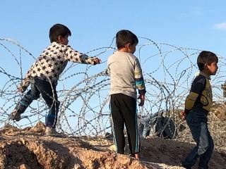 Kinder mit Stacheldraht in Kara Tepe